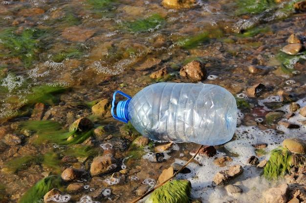 Plastikowa butelka wrzucona do wody. śmieci, odpady, zanieczyszczenie środowiska i natura.