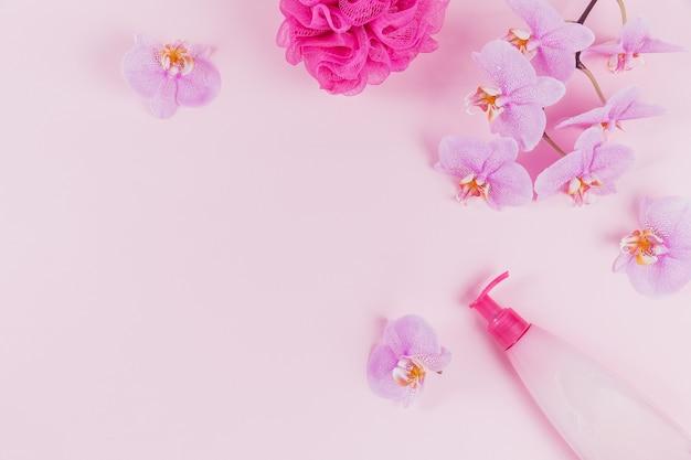 Plastikowa butelka z dozownikiem z mydłem kosmetycznym w płynie, żelem do mycia intymnego lub pod prysznic, fioletową gąbką i różowymi kwiatami orchidei na jasnoróżowej powierzchni