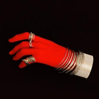 Plastikowa czerwona ręka w akcesoriach biżuterii mody.bransoletki i pierścionki. stylowa minimalistyczna koncepcja