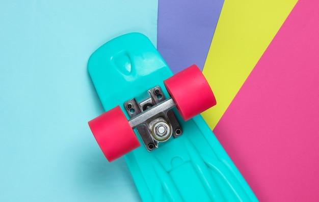 Plastikowa deska mini cruiser na kolorowym tle. trend w pastelowych kolorach. letnia zabawa. minimalistyczna koncepcja młodzieży. widok z góry
