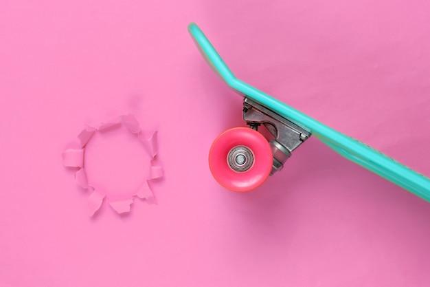 Plastikowa deska mini cruiser z rozdartym otworem. trend w pastelowych kolorach. letnia zabawa. minimalistyczna koncepcja młodzieży. widok z góry