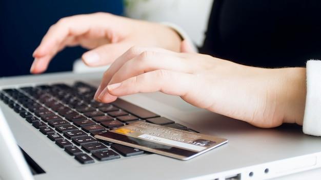 Plastikowa karta kredytowa leżącego na klawiaturze laptopa, podczas gdy młoda kobieta przegląda internet.