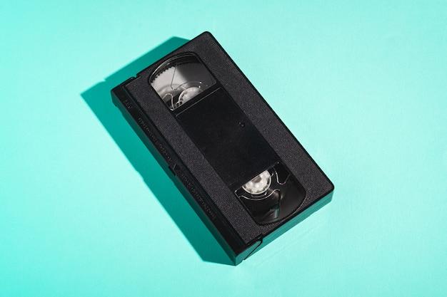 Plastikowa kaseta wideo w formacie vhs, magnetyczna taśma analogowa w stylu retro na minimalistycznej miętowej ścianie
