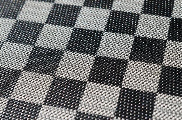 Plastikowa konsystencja w formie bardzo małej oprawy z tkaniny, pomalowana na czarno i szarość w stylu szachownicy