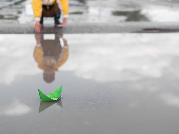 Plastikowa łódź i chłopiec w płaszczu przeciwdeszczowym