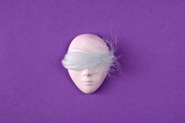 Plastikowa maska na twarz ozdobiona jasnoniebieskim piórkiem nad oczami na fioletowym tle