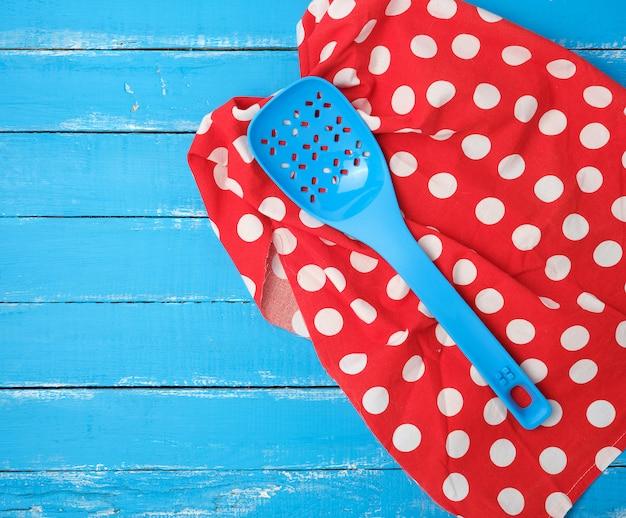 Plastikowa niebieska łyżka z otworami na czerwonej serwetce tekstylnej
