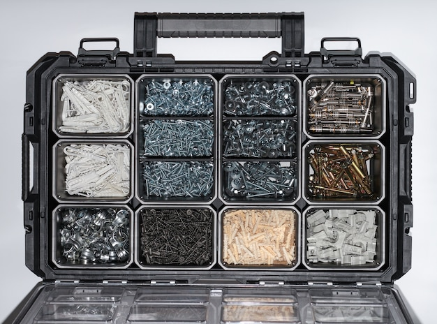 Plastikowa obudowa z elementami sprzętu z bliska. skrzynka narzędziowa ze śrubami, osprzętem, wkrętami samogwintującymi, gwoździami, klipsami, zszywkami, łącznikami, śrubami kotwiącymi
