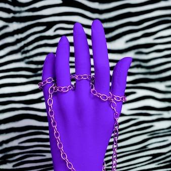 Plastikowa ręka w modnych akcesoriach jubilerskich na nadruku zebry. stylowa minimalistyczna koncepcja