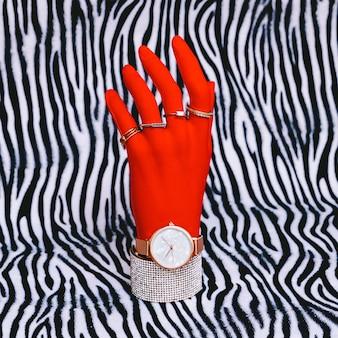 Plastikowa ręka w modnych akcesoriach jubilerskich. stylowa koncepcja