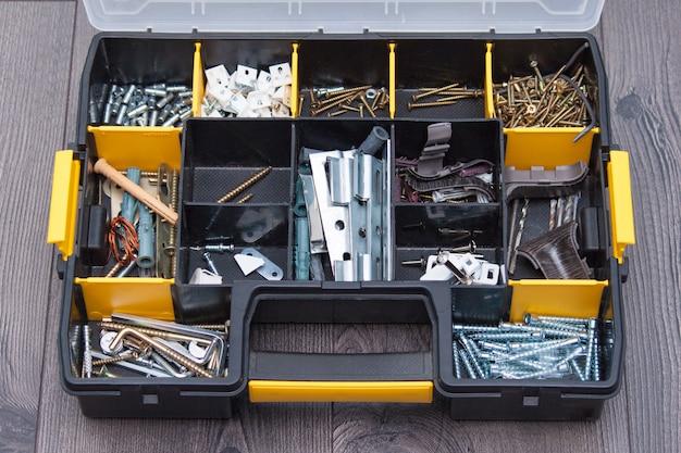 Plastikowa skrzynka z elementami sprzętu, zbliżenie. pudełko z gwoździami, śrubami, śrubami, kołkami.