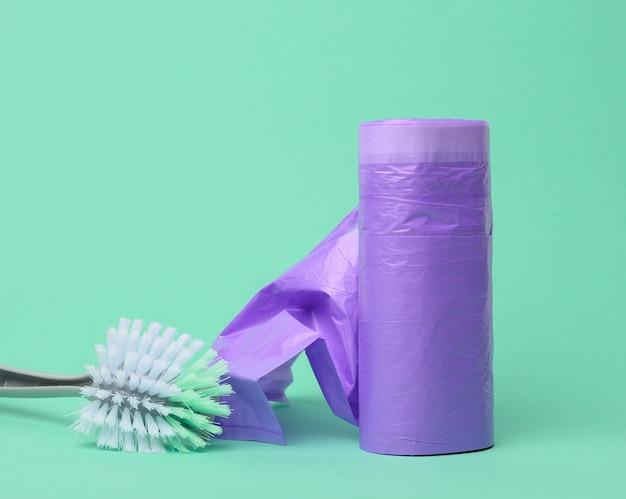 Plastikowa szczotka i motek fioletowych plastikowych worków na śmieci ze sznurkami na zielonym tle