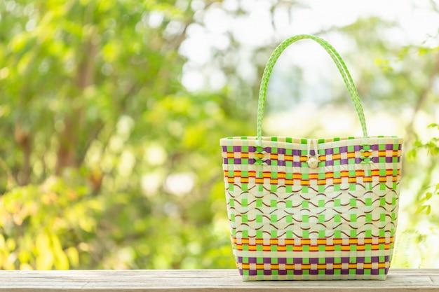 Plastikowa torba splotowa umieszczona na drewnianym stole z miejscem na tekst lub reklamę. torba może służyć do robienia zakupów, aby zastąpić plastikową torbę na zieleni