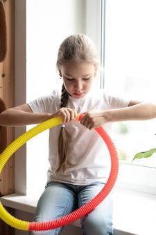 Plastikowa zabawka antystresowa sensoryczna w kształcie tuby w dziecięcych rękach. mała szczęśliwa dziewczynka bawi się w domu zabawką typu poptube fidget. dzieci trzymające i bawiące się popową rurką w kolorze żółtym i czerwonym, trend 2021 rok