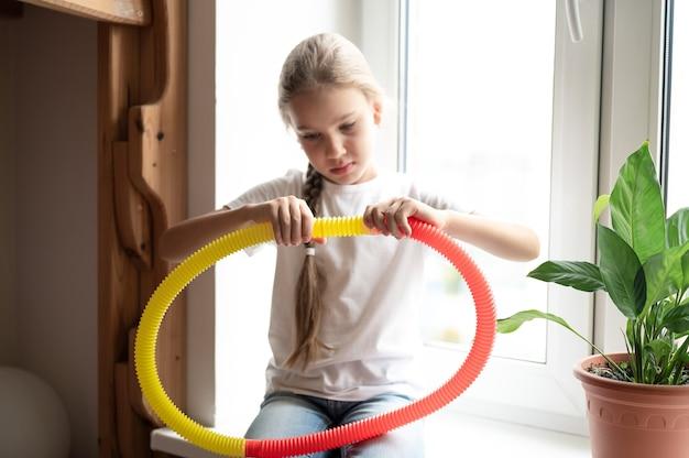 Plastikowa zabawka antystresowa sensoryczna w kształcie tuby w dziecięcych rękach. mała szczęśliwa dziewczynka bawi się w domu zabawką typu poptube fidget. dzieci trzymające i grające w popową rurkę w kolorze żółtym i czerwonym, trend 2021 rok