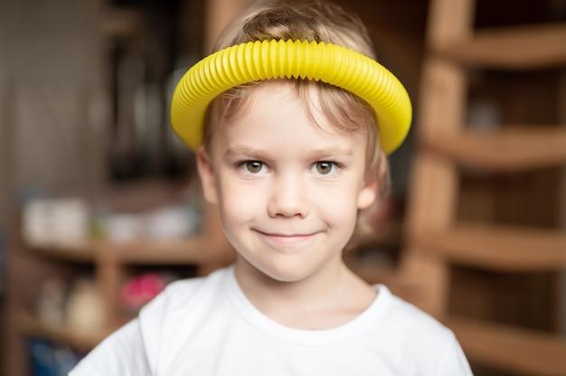 Plastikowa zabawka antystresowa sensoryczna w kształcie tuby w dziecięcych rękach. mały szczęśliwy chłopiec bawi się w domu zabawką typu poptube fidget. dzieci trzymające i grające w pop tube wielokolorowe kolory, trend 2021 rok