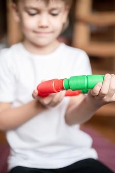 Plastikowa zabawka antystresowa sensoryczna w kształcie tuby w dziecięcych rękach. mały szczęśliwy chłopiec bawi się w domu zabawką typu poptube fidget. dzieci trzymające i grające w popową rurkę w kolorze czerwonym i zielonym, trend 2021 rok