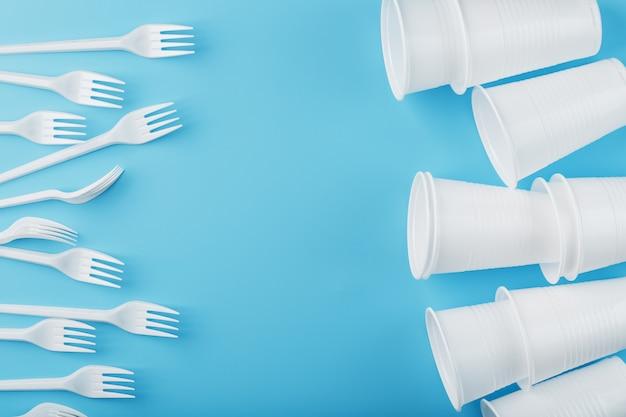 Plastikowa zastawa stołowa na błękitnej ścianie. widelce i szklanki jednorazowe z wolną przestrzenią.