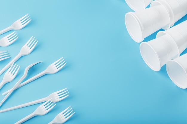Plastikowa zastawa stołowa na niebiesko. widelce i szklanki jednorazowe z wolną przestrzenią.