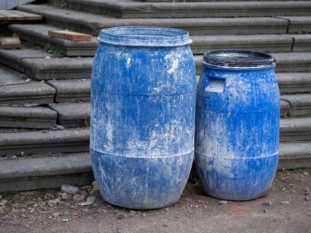 Plastikowe beczki niebieskie na placu budowy.
