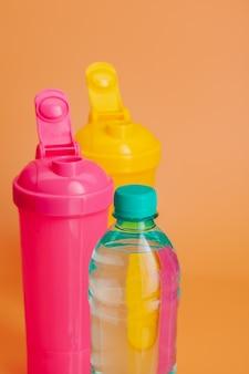 Plastikowe bidony na pastelowym beżu