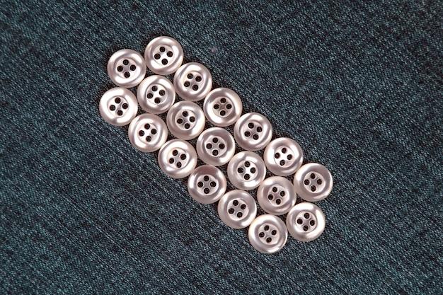 Plastikowe błyszczące guziki na ubrania na tle tkaniny. moda i odzież. przemysł fabryczny.