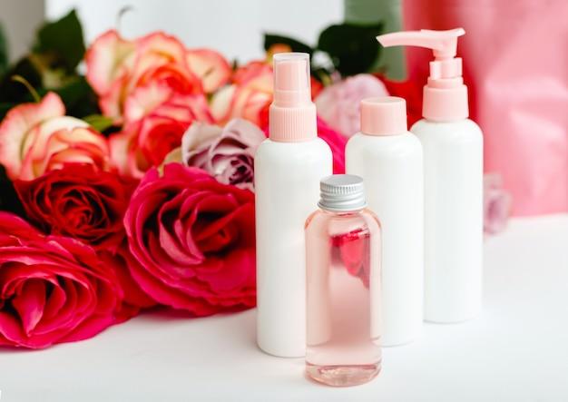 Plastikowe butelki kosmetyczne, serum, mydło, olej na białym stole kwiatowym. kwiat czerwony różowy róż naturalny organiczny produkt kosmetyczny. spa, pielęgnacja skóry, kąpiele na ciało. zestaw kosmetyków w kolorze różowym z różą.