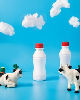 Plastikowe butelki mleka, krowy zabawkowe i chmury