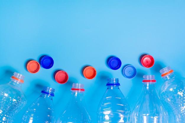 Plastikowe butelki na błękitnym tle. recykling, ratowanie ziemi koncepcja problemów środowiskowych