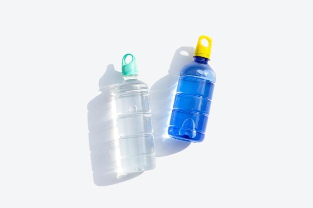 Plastikowe butelki na wodę na białej powierzchni.