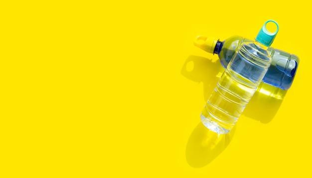 Plastikowe butelki na wodę na żółtej powierzchni
