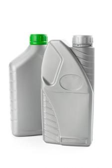 Plastikowe butelki od olejów samochodowych odizolowywających na bielu