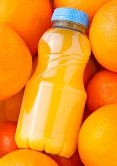 Plastikowe butelki organicznie świeży sok pomarańczowy z surowym pomarańcze tłem