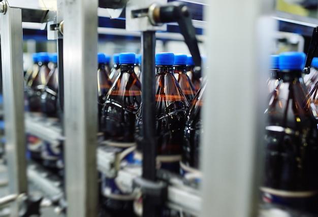 Plastikowe butelki pet z żółtego plastiku z niebieskimi wieczkami z piwem lub słodkimi napojami na przenośniku taśmowym na tle fabryki. przemysłowa produkcja napojów.