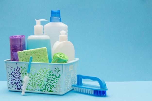 Plastikowe butelki płynu do mycia naczyń, czyszczenia szkła i płytek w koszu, gąbka, worki na śmieci i szczotka na niebieskim tle. zestaw do mycia i czyszczenia.