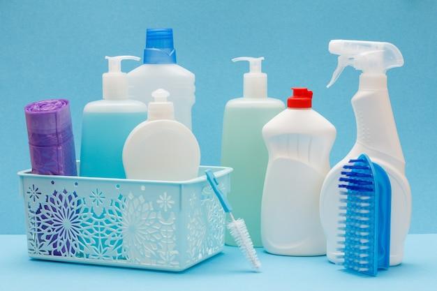 Plastikowe butelki płynu do mycia naczyń, czyszczenia szkła i płytek w koszu, gąbki, worki na śmieci i szczotki na niebieskim tle. koncepcja mycia i czyszczenia.