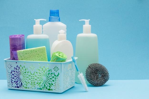 Plastikowe butelki płynu do mycia naczyń, czyszczenia szkła i płytek w koszu, gąbki, worki na śmieci na niebieskim tle. koncepcja mycia i czyszczenia.