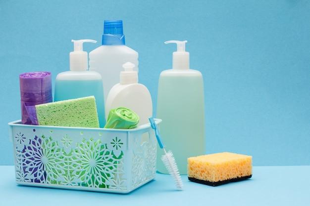 Plastikowe butelki płynu do mycia naczyń, czyszczenia szkła i płytek w koszu, gąbki, worki na śmieci na niebieskim tle. zestaw do mycia i czyszczenia.