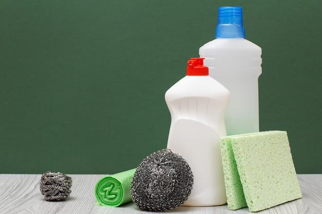 Plastikowe butelki płynu do mycia naczyń, detergentu do kuchenek mikrofalowych i kuchenek, gąbki i worki na śmieci na zielonym tle. koncepcja mycia i czyszczenia.