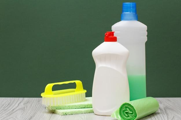Plastikowe butelki płynu do mycia naczyń, detergentu do kuchenek mikrofalowych i kuchenek, szczotki, gąbek i worków na śmieci na zielonym tle. koncepcja mycia i czyszczenia.