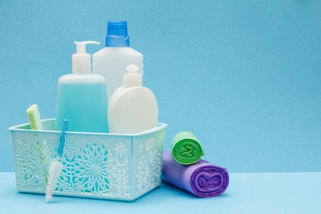 Plastikowe butelki płynu do mycia naczyń, środek do czyszczenia szkła i płytek w koszu, gąbki i worki na śmieci na niebieskim tle. zestaw do mycia i czyszczenia.