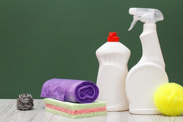 Plastikowe butelki płynu do mycia naczyń, środek do czyszczenia szkła i płytek, worki na śmieci, gąbki na zielonym tle. koncepcja mycia i czyszczenia.