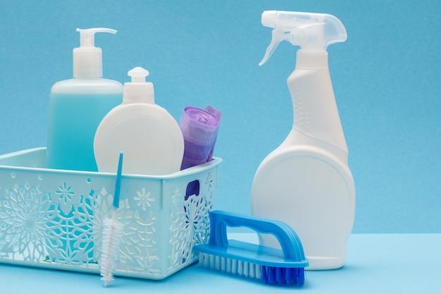 Plastikowe butelki płynu do mycia naczyń, środek do czyszczenia szkła i płytek, worki na śmieci w koszu i szczotki na niebieskim tle. koncepcja mycia i czyszczenia.