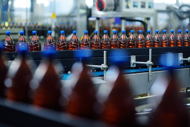 Plastikowe butelki po piwie na przenośniku taśmowym w tle browaru