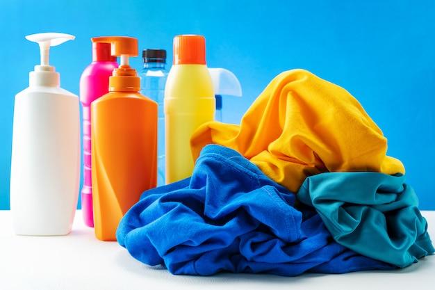Plastikowe butelki środków czyszczących ustawione w stos ubrań na białym stole niebieski