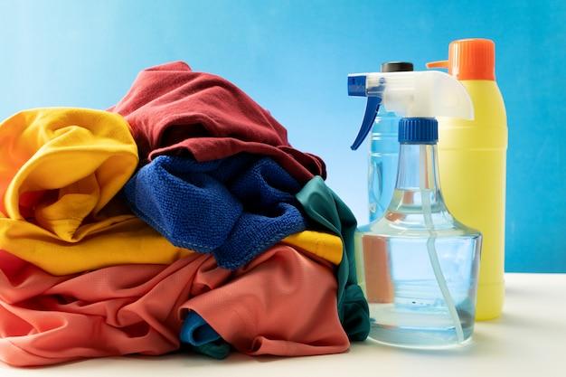 Plastikowe butelki środków czyszczących ustawione w stos ubrań na białym stole