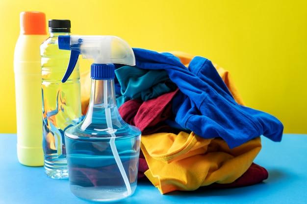 Plastikowe butelki środków czyszczących ustawione w stos ubrań na niebieskim stole żółty
