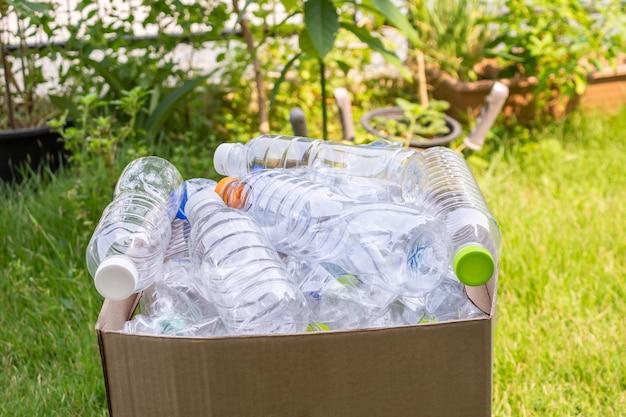 Plastikowe butelki w brązowym pojemniku na śmieci do recyklingu