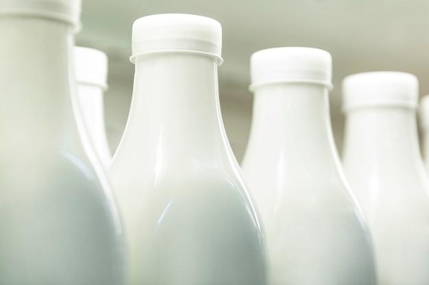 Plastikowe butelki z mlekiem na półce w sklepie. zdrowe odżywianie. zbliżenie.