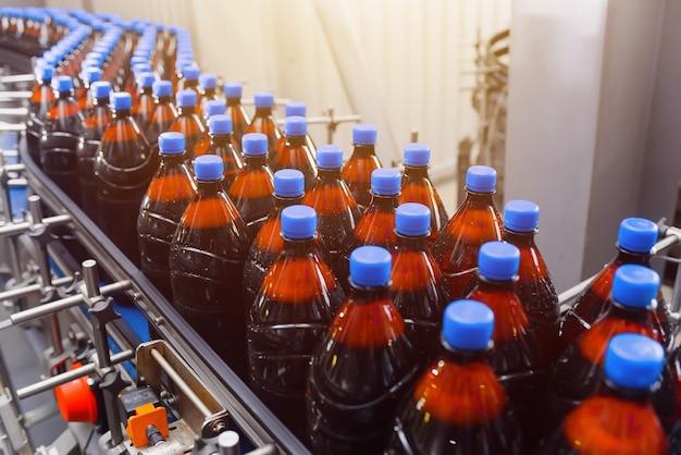 Plastikowe butelki z piwem na przenośniku taśmowym.
